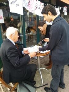 Bir öğrenci iki oturum arasında Teziç'e Anayasa Hukuku kitabını imzalatıyor.