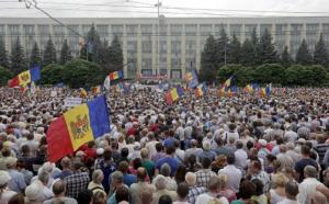 "Protesters carry Moldova's national flags during an anti-government rally, organised by the civic platform ""Dignity and Truth"", in central Chisinau"