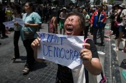 """TOPSHOTS An anti coup protester screams at soldiers (not seen) as she holds a piece of paper that reads """"we want democracy"""" during a planned gathering in Bangkok on May 25, 2014. Thailand's military junta said it had disbanded the Senate and placed all law-making authority in the hands of the army chief, dramatically tightening its grip after a coup that has sparked Bangkok protests and drawn international condemnation. AFP PHOTO/ Nicolas ASFOURI"""